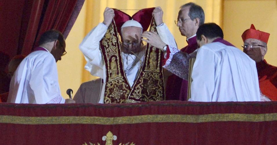 13.mar.2013 - O cardeal argentino Jorge Mario Bergolio, eleito o novo papa da Igreja Católica, aparece na sacada da basílica de São Pedro, no Vaticano, acena para a multidão aglomerada na praça São Pedro e coloca o manto de sumo pontífice