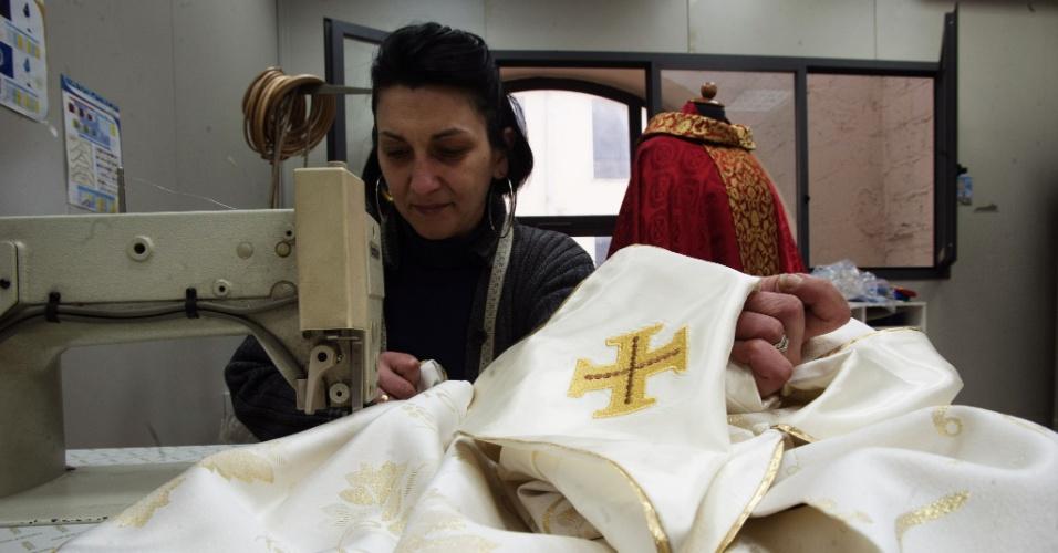 14.mar.2013 - Costureira faz ajustes na vestimenta sagrada do novo papa, nesta quinta-feira (14). A roupa será usada pelo papa Francisco durante a sua primeira missa aberta no Vaticano, prevista para a próxima terça-feira (19)
