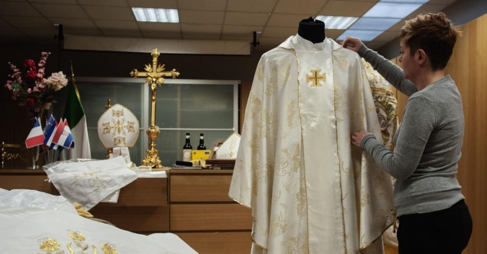 14.mar.2013 - Costureira faz ajustes na vestimenta sagrada do novo papa, nesta quinta-feira (14), em Nápoles, na Itália. A roupa será usada pelo papa Francisco durante a sua primeira missa aberta no Vaticano, prevista para a próxima terça-feira (19)