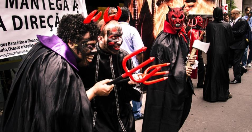 14.mar.2013 - Fantasiados de diabos, funcionários do Banco do Brasil protestam diante da agência do banco na esquina da avenida Paulista com a rua Augusta