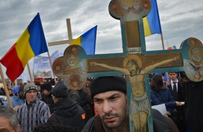 14.mar.2013 - Fiéis ortodoxos carregam a bandeira romena e uma réplica da cruz de Cristo durante protesto contra a implantação da identificação por meio de chips em frente à sede do Parlamento em Bucareste, capital do país