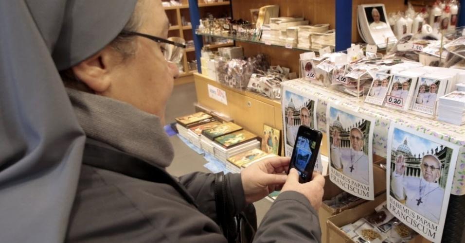 14.mar.2013 - Freira fotografa os santinhos do papa Francisco expostos na loja oficial do Vaticano, nesta quinta-feira (14)