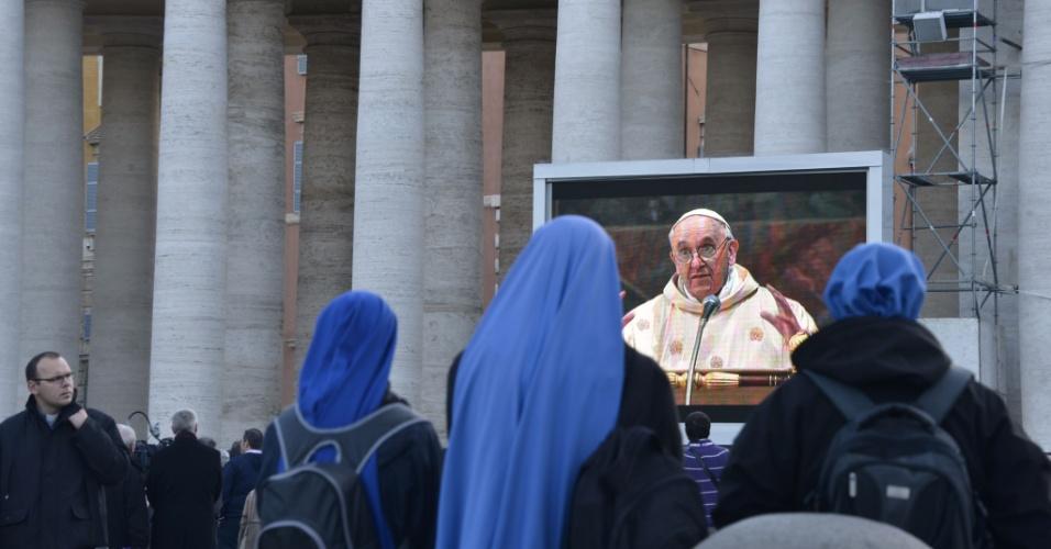 14.mar.2013 - Freiras assistem à missa do papa Francisco, a primeira celebrada na Capela Sistina, no telão instalado na praça São Pedro, no Vaticano