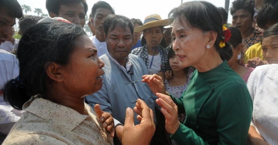 14.mar.2013 - Liderança opositora de Mianmar, Aung San Suu Kyi (direita), conversa com aldeões durante visita a um projeto de mineração de cobre em Monywa, no norte do país