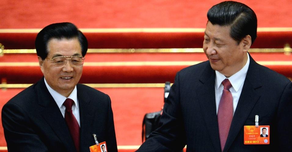 14.mar.2013 - O presidente recém-eleito da China, Xi Jinping (à direita) cumprimenta o ex-presidente, Hu Jintao, após Xi ser escolhido para presidir também a Comissão Central Militar, durante o 12º Congresso Nacional Popular, em Pequim. Xi se tornou presidente do país mais populoso do mundo via voto de parlamentares
