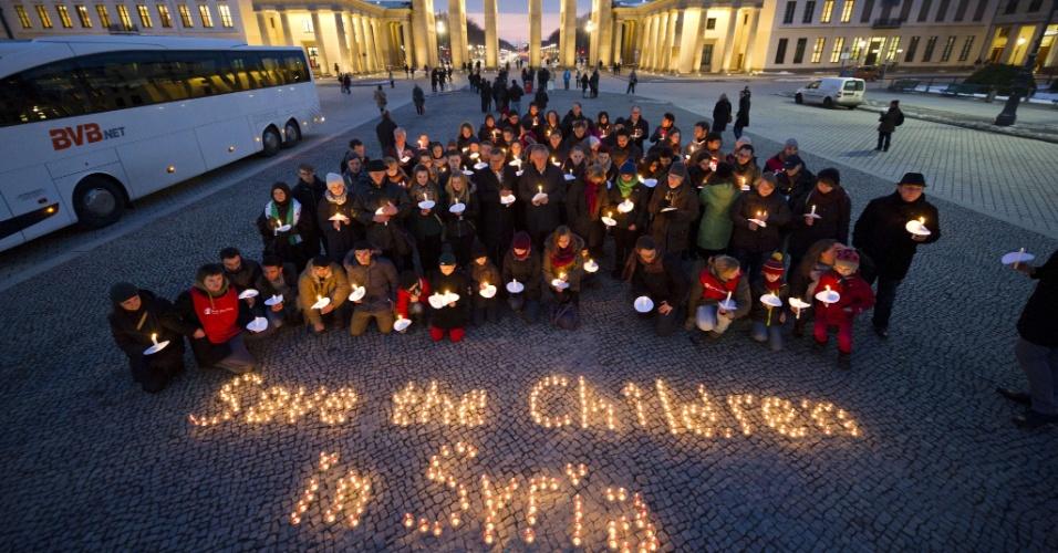 """14.mar.2013 - Velas acesas formam a frase """"Save the children in Syria"""" (Salvem as crianças da Síria, em inglês), nesta quinta-feira (14), em Berlim. O ato foi organizado pela organização internacional Save the Children. A Síria vive uma guerra civil que tem vitimado também mulheres e crianças"""