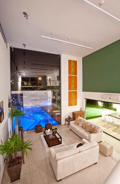 """O fechamento em vidro que se volta para a piscina, a partir da sala de estar, leva sistema """"spiderglass"""" (Blindex). O """"spiderglass"""" permite o uso de enormes panos em vidro espesso, com 12 mm, por possuir travas metálicas aplicadas diretamente no vidro, o que dá sustentação estrutural ao fechamento. A casa Acapulco foi criada pelo arquiteto Flavio Castro"""
