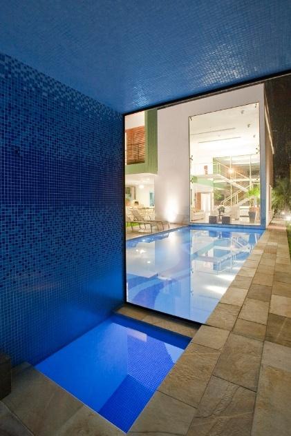 Na sauna, as pastilhas de vidro (Kolorines) repetem padrões desenhados pelo arquiteto Flavio Castro, projetista da casa Acapulco, em três tons de azul. O vidro (Blindex) que separa a sauna da piscina está encaixado no piso, que é por sua vez revestido de pedra Miracema (Pedras Bandeirantes)