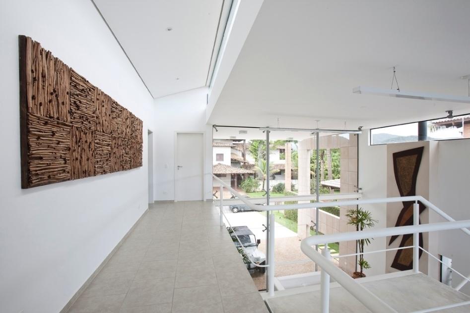 """O corredor de distribuição dos dormitórios no pavimento superior da casa Acapulco, do arquiteto Flavio Castro, liga os dois quartos dispostos em cada extremidade. Dali, é possível avistar a fachada da frente que leva sistema """"spiderglass"""" e prevê enormes panos em vidro espesso, de 12 mm. O """"spiderglass"""" tem travas metálicas dispostas diretamente no vidro, o que dá sustentação estrutural ao fechamento"""