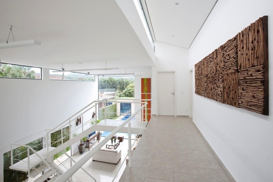 O corredor de distribuição dos dormitórios no pavimento superior da casa Acapulco, do arquiteto Flavio Castro, é decorado com um quadro da artista Nilza Rezende, feito em pau de canela. O corredor recebe iluminação zenital por uma fenda envidraçada a partir de um forro de gesso inclinado, que contém iluminação dicroica embutida. O piso é de porcelanato (Eliane)