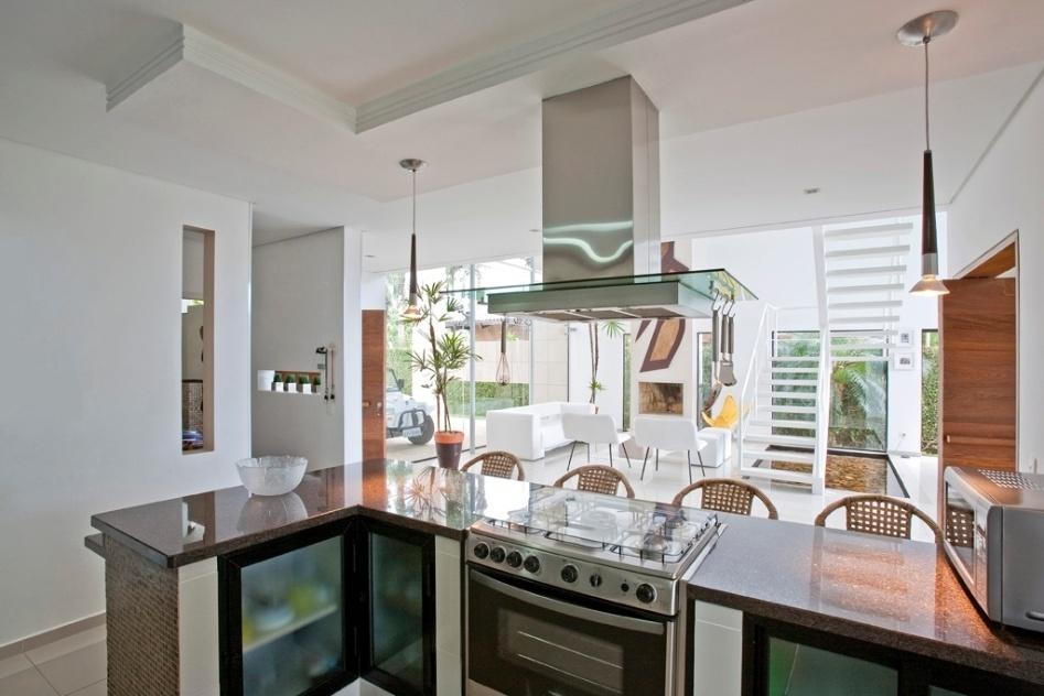 Na cozinha, pendentes com lâmpadas halopar 20 iluminam o tampo de granito café imperial da bancada (Pedras Bandeirantes). As pastilha de vidro (Kolorines) que revestem a altura da bancada têm três tons de marrom, enquanto as portas de alumínio (Alcoa) levam vidro aramado (Blindex). O projeto de Flavio Castro para casa Acapulco, foi construído no Guarujá (SP)