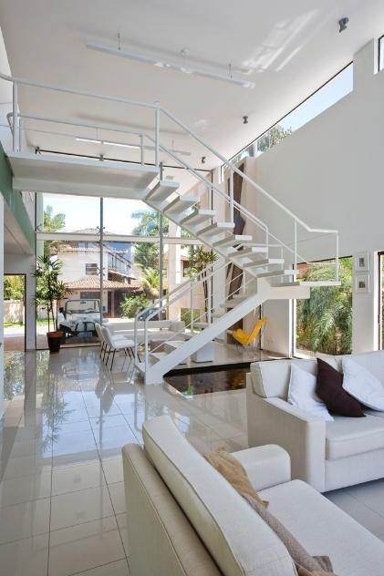 """A fachada frontal da casa Acapulco, projetada pelo arquiteto Flavio Castro, também é fechada em vidro no eixo longitudinal, que se comunica com área social e piscina e se estende até o pavilhão dos fundos, onde está a sauna. A iluminação das salas de estar e da lareira oferece opções de cenários. Réguas desenvolvidas em perfis de chapa metálica """"U"""", para lâmpadas frias, produzem luz menos cenográfica e voltada para o teto, o design das luminárias é assinado pelo arquiteto"""