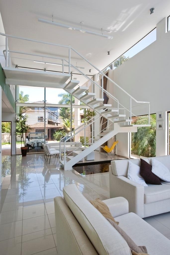 A fachada frontal da casa Acapulco, projetada pelo arquiteto Flavio Castro, também é fechada em vidro no eixo longitudinal, que se comunica com área social e piscina e se estende até o pavilhão dos fundos, onde está a sauna. A iluminação das salas de estar e da lareira oferece opções de cenários. Réguas desenvolvidas em perfis de chapa metálica