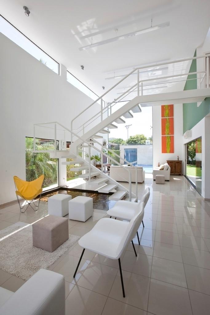 A área social é uma sucessão de três salas com pé direito duplo (5,5 m) com único elemento divisório: uma escada para circulação vertical, sob a qual está o espelho d'água. Os fechamentos em vidro ao fundo, voltados para a piscina, e laterais, direcionados ao corredor, são pontos estratégicos que garantem máxima iluminação natural pela manhã, além de ventilação. A casa Acapulco foi projetada pelo arquiteto Flavio Castro, no Guarujá