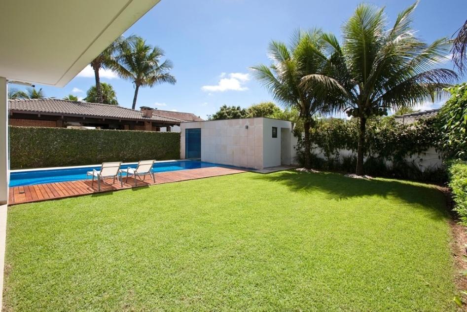 """O pavilhão, nos fundos do terreno da residência Acapulco, no Guarujá, abriga a casa de máquinas para piscina, vestiário e a sauna. A área gramada é o """"recreio"""" - um dos """"vazios"""" construtivos previstos pelo arquiteto Flavio Castro para servir de apoio à área de lazer. Além de toda vegetação circundante, compostas por trepadeiras nos muros e paineiras, o anexo possui telhado verde (grama)"""