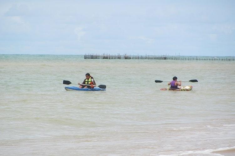 Crianças brincam em caiaques na praia Sonho Verde