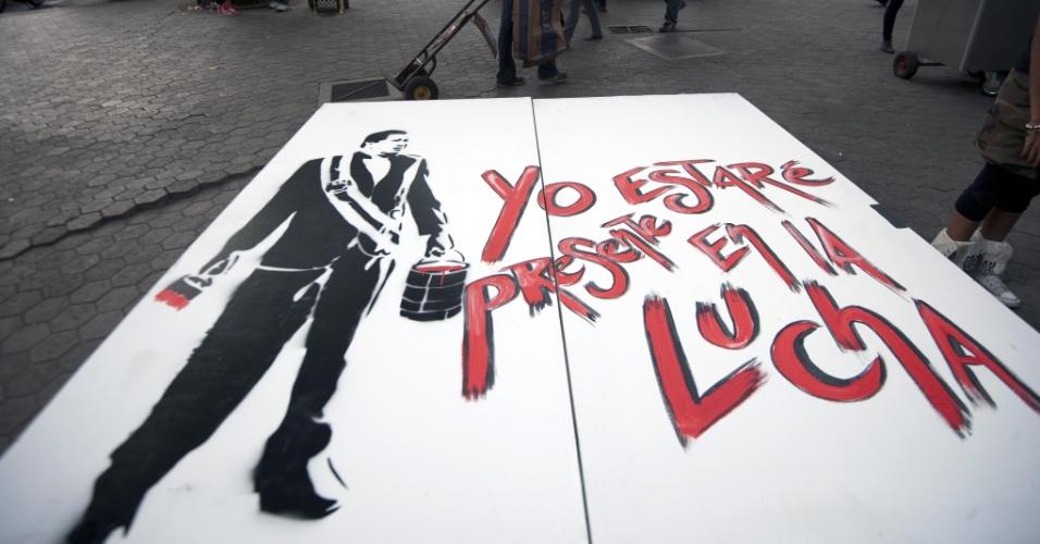 13.mar.2013 - Visitantes da Feira Internacional do Livro da Venezuela, que ocorre em Caracas, caminham perto de um pôster em homenagem a Hugo Chávez, que morreu no último dia 5 de março, aos 58 anos, vítima de um câncer na região pélvica