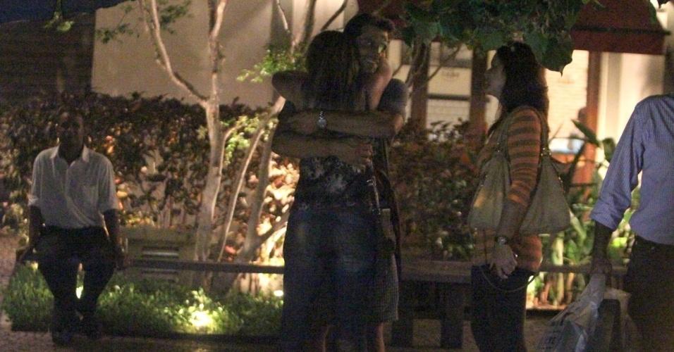 14.mar.2013 - Henry Castelli abraça amiga em pizzaria na Barra da Tijuca, Rio de Janeiro