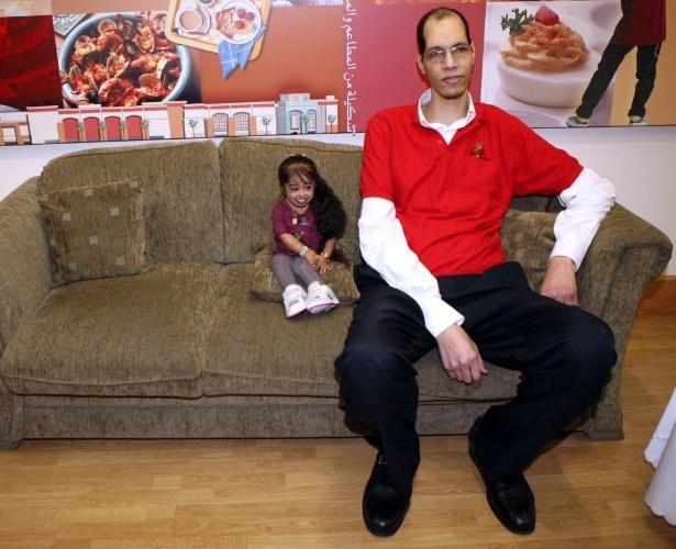 14.mar.2013 - Indiana Jyoti Amge, 19, menor mulher do mundo segundo o Guinness, se senta ao lado do marroquino Brahim Takioullah, dono do maior pé do mundo, durante evento promovido pelo livro mundial dos recordes na cidade do Kuait