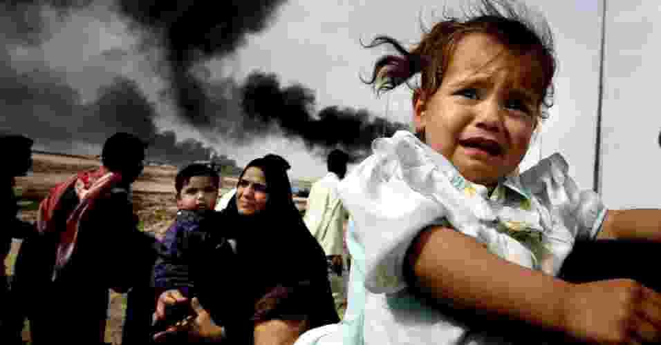 30.mar.2003 - Criança iraquiana chora enquanto sua família deixa a cidade de Basra, no sul do Iraque, por meio de uma das pontes locais, controladas por tropas britânicas - Dan Chung/AFP