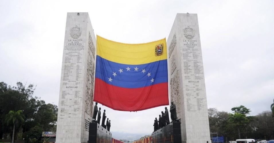 15.mar.20123 - Bandeira gigante da Venezuela é hasteada no Paseo de Los Próceres, em Caracas, local onde passará o caixão de Hugo Chávez - o cortejo até um museu militar vai percorrer mais de 18 quilômetros na capital venezuelana