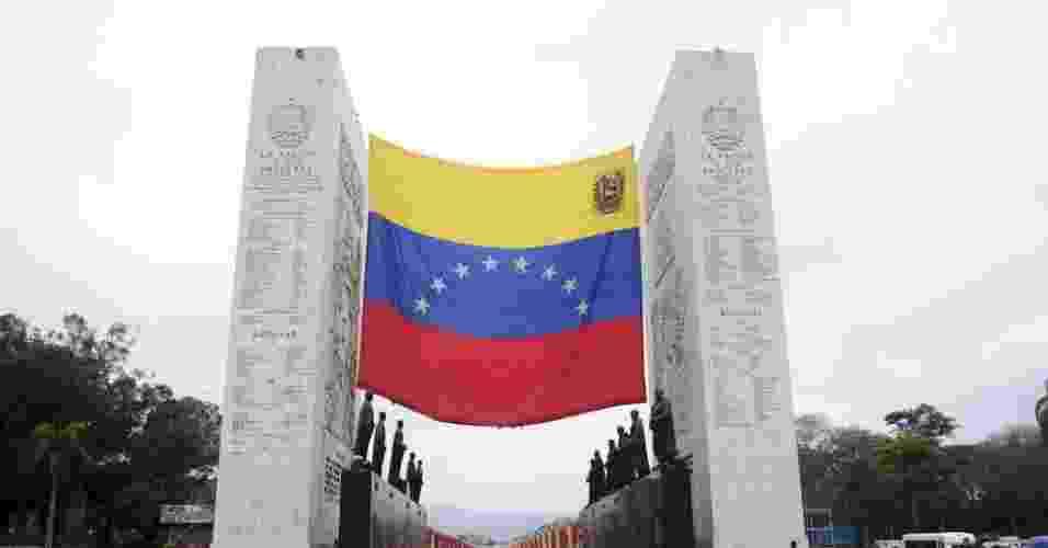 15.mar.20123 - Bandeira gigante da Venezuela é hasteada no Paseo de Los Próceres, em Caracas, local onde passará o caixão de Hugo Chávez - o cortejo até um museu militar vai percorrer mais de 18 quilômetros na capital venezuelana - William Viera/Efe