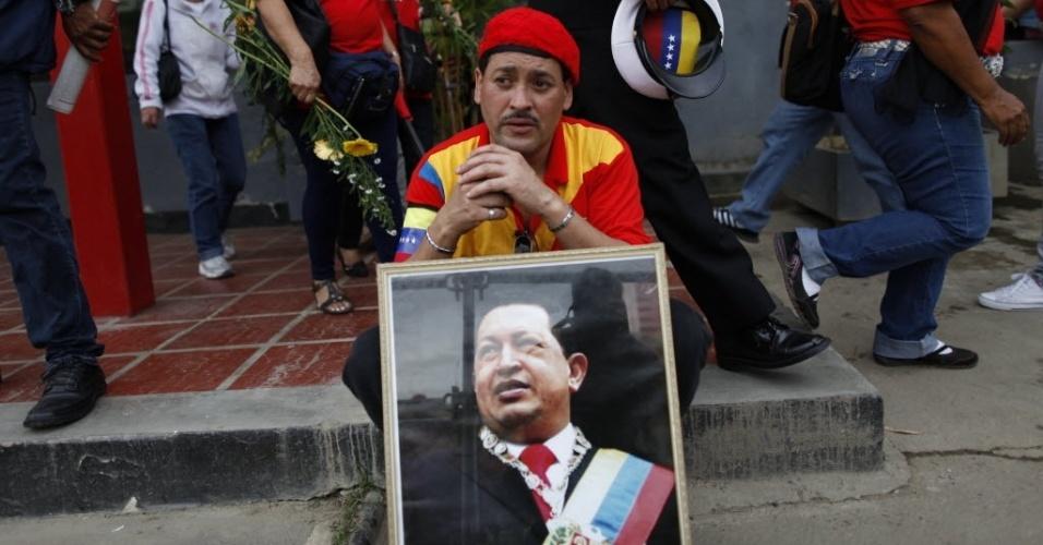 15.mar.20123 - Homem com imagem de Hugo Chávez espera no Paseo de Los Próceres, em Caracas, na Veneuela, para ver a transferência do caixão de Hugo Chávez - o cortejo até um museu militar vai percorrer mais de 18 quilômetros na capital venezuelana