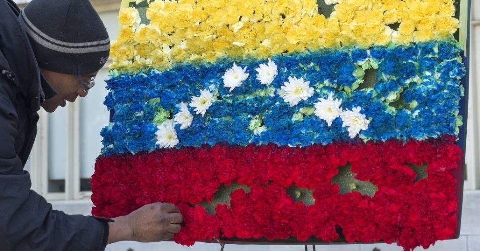 15.mar.2013 - Cinegrafista arruma flores dispostas no formato da bandeira da Venezuela diante da estátua de Simón Bolívar, no jardim da sede da Organização dos Estados Americanos (OAS, na sigla em inglês), em Washington, nos Estados Unidos. O Conselho Permanente da OAS prestou homenagem a Hugo Chávez com flores e um minuto de silêncio