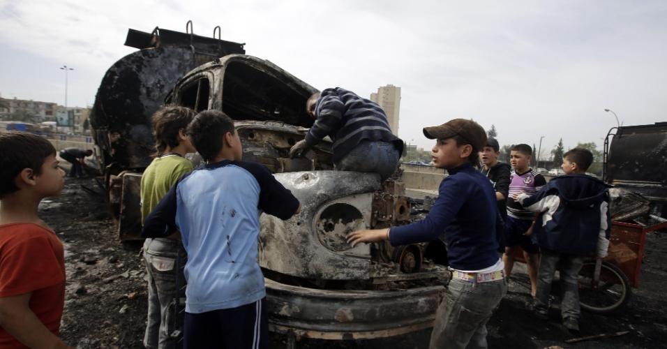 15.mar.2013 - Crianças brincam perto de caminhões queimados em Trípoli, capital da Líbia, nesta sexta-feira (15). Sete veículos que levavam combustível para a Síria foram interceptado e depredados na noite de quinta-feira (14) por opositores do regime do sírio Bashar Al-Assad, segundo agências de notícias