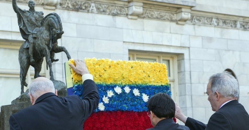 15.mar.2013 - José Miguel Insulza (à esquerda), secretário-geral da Organização dos Estados Americanos (OAS, na sigla em inglês), Denis Moncada (centro), presidente do Conselho Permanente, e Roy Chaderton (à direita), embaixador venezuelano do órgão, colocam uma bandeira de flores aos pés da estátua de Símon Bolívar, que fica no jardim da sede em Washington, nos Estados Unidos