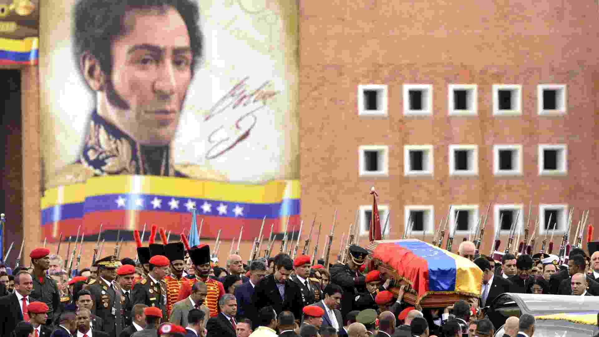 """15.mar.2013 - O caixão com o corpo do presidente Hugo Chávez, morto em 5 de março, é carregado durante o translado que o transportou da Academia Militar de Caracas até o Museu Histórico Militar, onde o governo da Venezuela anunciou a intenção de embalsamá-lo para ficar exposto ao público. Ao fundo, um mural estampa o rosto de Simón Bolívar, herói da independência venezuelana e ídolo de Chávez, que batizou em sua homenagem o movimento político do """"bolivarianismo"""" - Leo Ramirez/AFP"""