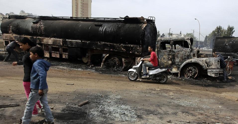 15.mar.2013 - Pessoas passam próximas a caminhões queimados em Trípoli, capital da Líbia, nesta sexta-feira (15). Sete veículos que levavam combustível para a Síria foram interceptado e depredados na noite de quinta-feira (14) por opositores do regime do sírio Bashar Al-Assad, segundo agências de notícias