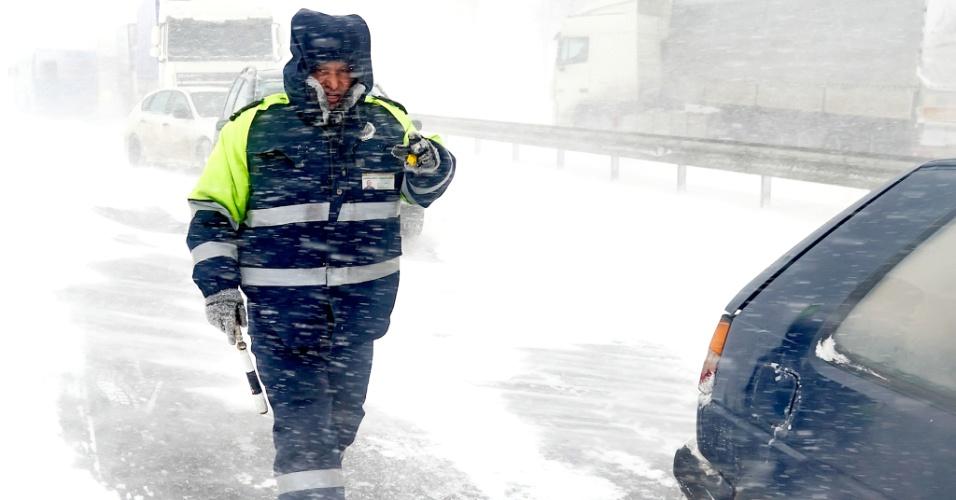 15.mar.2013 -  Policial de tráfego enfrenta dificuldade para trabalhar sob forte nevasca, neste sábado (16), em rodovia que liga Minsk (Belarus) a Moscou (Rússia). A temperatura na região chegou a -6ºC, incomum para esta época do ano