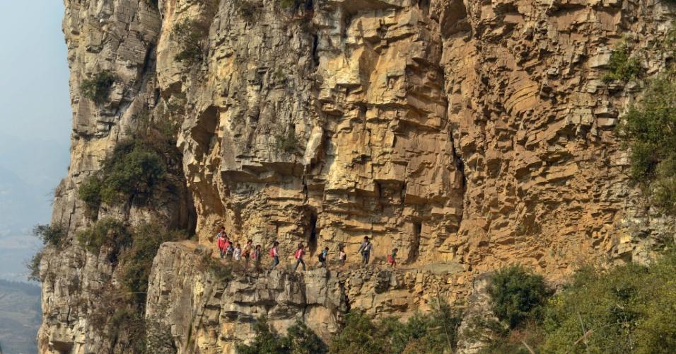16.mar.2013 -  Imagem divulgada neste sábado mostra o diretor de escola Xu Liangfan levando  seus alunos do ensino primário da aldeia chinesa de Bijie por um caminho perigoso e estreito, em um penhasco. O grupo faz o longo percurso todos os dias para chega à escola