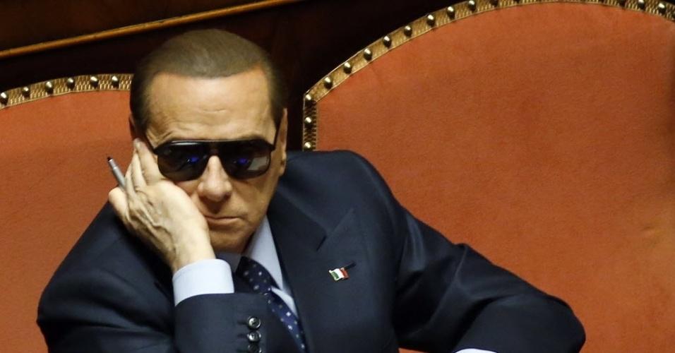 """16.mar.2013 - O ex-primeiro-ministro italiano Silvio Berlusconi, que está para ser julgado por fraude fiscal e um escândalo sexual, xingou um grupo de manifestantes que o vaiaram e assobiaram quando ele entrava no Parlamento, neste sábado (16), para participar da eleição do presidente do Senado. """"Vocês deveriam ter vergonha, vocês são pobres, tolos e estúpidos"""", disse em voz alta enquanto seguia para o Senado"""