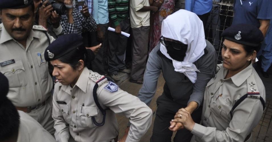 16.mar.2013 - Turista suíça, vítima de um estupro em grupo diante do marido, em uma floresta na Índia, é levada com o rosto coberto para fazer exames em um hospital, neste sábado (16)