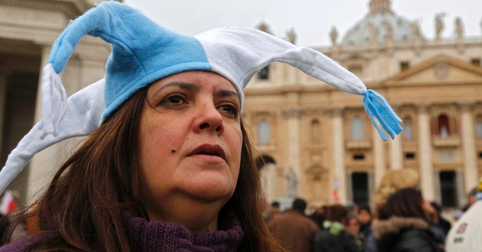 17.mar.2013 - Mulher com chapéu com ar cores da bandeira da argentina acompanha na praça São Pedro, no Vaticano, o primeiro Angelus do papa Francisco
