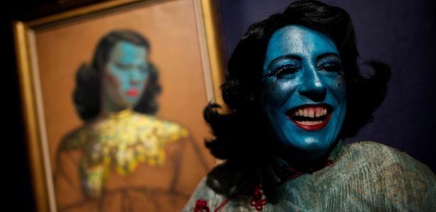 """Cantora de cabaret Tricity Vogue, se veste como a personagem senhora azul, inspirada na pintura """"Menina Chinesa"""" (ao fundo), do artista Vladimir Tretchikoff, na casa de leilões Bonhams, em Londres, no Reino Unido - Andrew Cowie/AFP"""