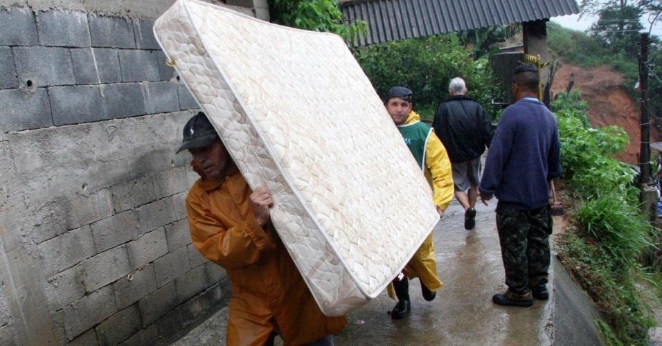 18.mar.2013 - Homens carregam colchão no bairro Quitandinha, em Petrópolis (RJ), onde a chuva provocou deslizamentos de terra e o desabamento de imóveis