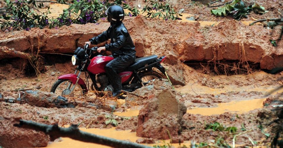 18.mar.2013 - Motociclista passa por área afetada por deslizamento de terra no bairro Quitandinha, em Petrópolis (RJ)