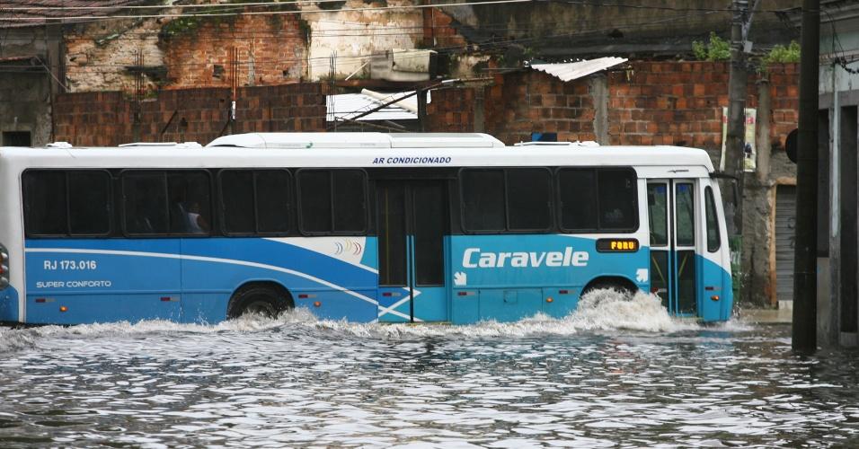 18.mar.2013 - Ônibus circula por área alagada na rua da Gamboa, próximo à cidade do Samba, na zona portuária do Rio de Janeiro