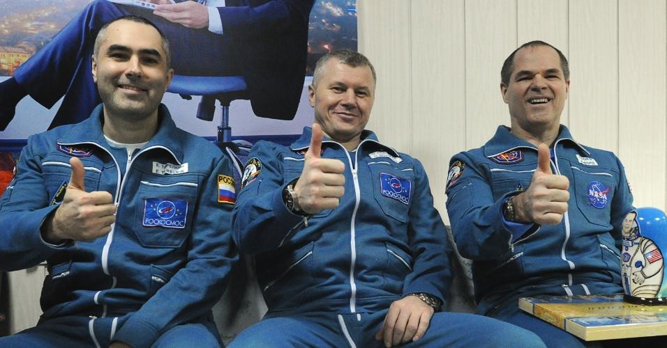 18.mar.2013 - Os cosmonautas russos Evgeny Tarelkin, Oleg Novitskiy e o astronauta norte-americano Kevin Ford (da esquerda para direita) indicam que estão bem enquanto posam para os fotógrafos no aeroporto de Kostanay, no Cazaquistão. Após quase cinco meses na Estação Espacial Internacional, o trio voltou à Terra a bordo da cápsula Soyuz na madrugada de sábado (16) - a nave russa