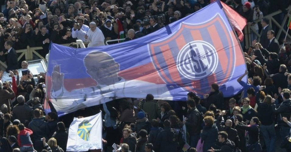 19.mar.2013 - Fiéis estendem bandeira do San Lorenzo, time pelo qual torce o papa Francisco (à frente da bandeira), na chegada do Sumo Pontífice à praça de São Pedro, no Vaticano, para a missa inaugural de seu papado