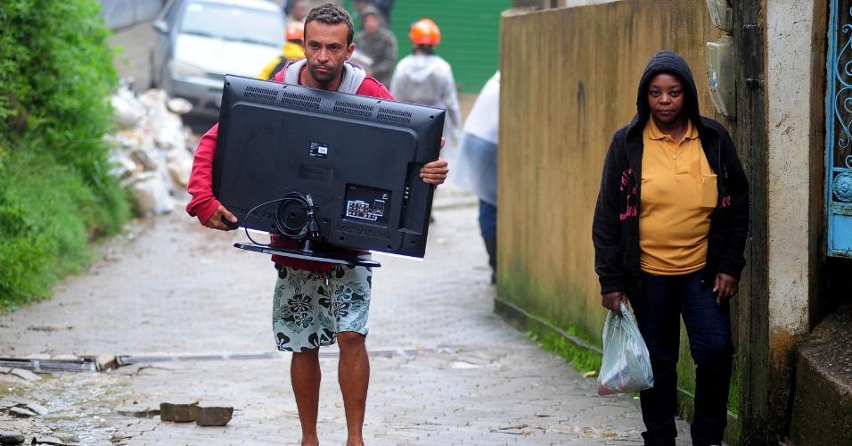 19.mar.2013 - Moradores retiram seus pertences de casa, em Petrópolis (RJ), atingida pelas fortes chuvas dos últimos dias. Segundo a Defesa Civil Estadual, pelo menos 17 pessoas morreram após o deslizamentos de terra na região, causado pelo temporal que atingiu o Estado do Rio de Janeiro entre domingo (17) e segunda-feira (18)