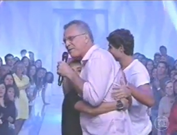 """19.mar.2013 - Bial não conseguiu cumprimentar André direito, pois um fã invadiu o palco e agarrou o apresentador. """"Bial, eu sou muito seu fã, eu te amo Bial"""", falava o adolescente. """"Alguém me ajuda com esse menino"""", pediu o apresentador para a produção. Desconfortável, Pedro Bial abraçou de volta o fã e deu um beijo na testa"""