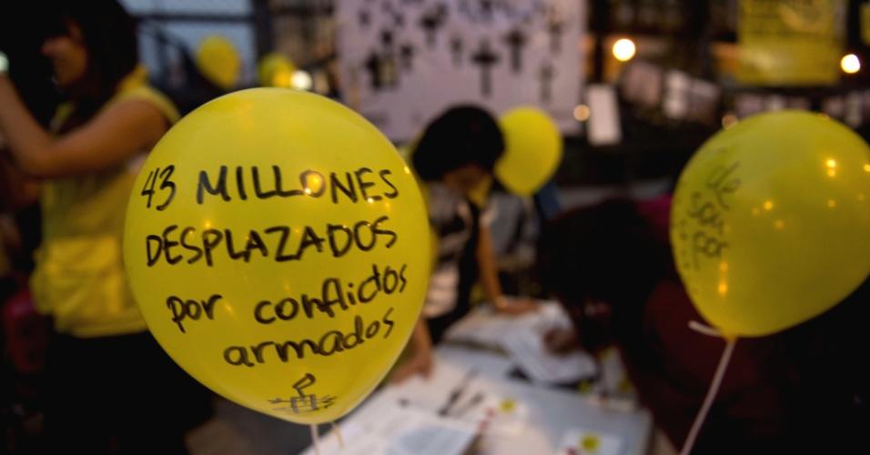 """19.mar.2013 - Ativistas da Anistia Internacional protestam diante da embaixada dos EUA na Cidade do México. Eles exigem que o presidente Barack Obama assuma a responsabilidade do tratado de negociação de armas, discutido no parlamento norte-americano. No balão, se lê: """"43 milhões deslocados devido a conflitos armados"""""""