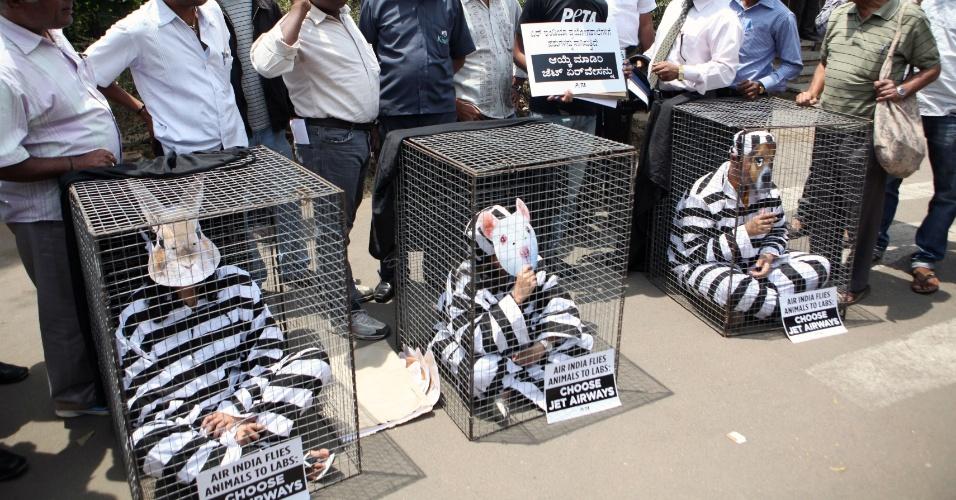 20.mar.2013 - Ativistas da ONG Peta, que defende o direito dos animais, vestidos de presidiários, se trancam em gaiolas durante protesto em Bangalore, na Índia