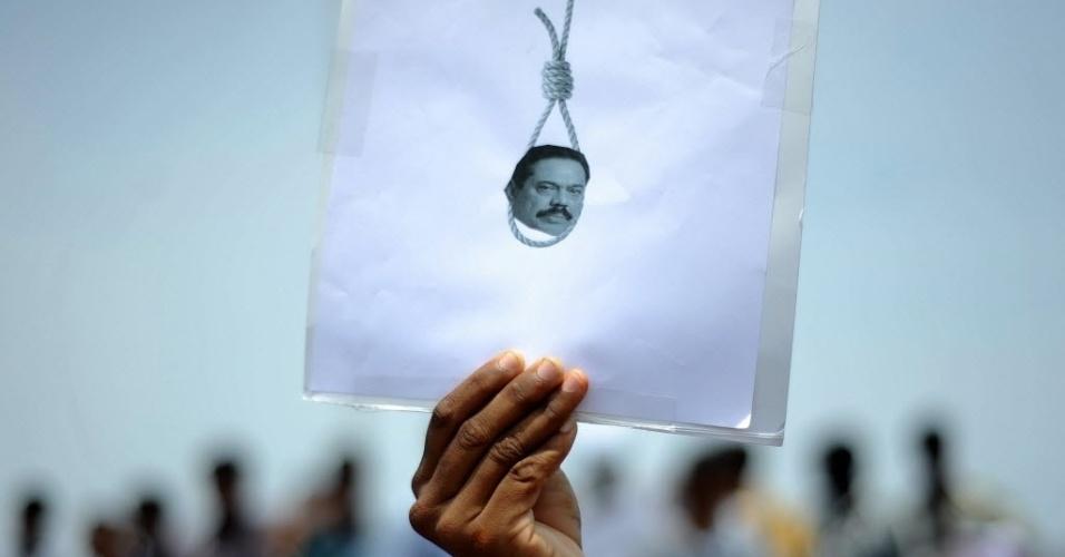 20.mar.2013 - Estudante exibe cartaz com imagem do presidente do Sri Lanka, Mahinda Rajapakse, durante manifestação para denunciar os crimes de guerra cometidos contra o grupo separatista Tigres Tâmeis, em Chennai, no Sri Lanka