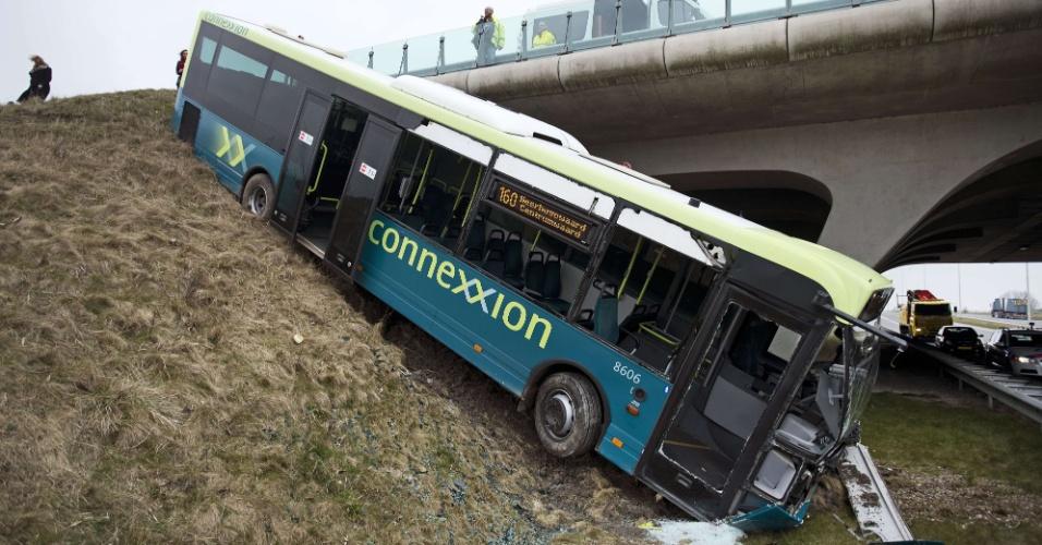20.mar.2013 - Ônibus de transporte público da empresa Connexxion sai da pista e fica pendurado em barranco em Alkmaar, na Holanda. Por conta do acidente, a rodovia N242 foi parcialmente fechada
