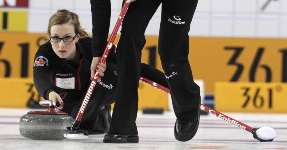 20.mar.2013 - Alison Kreviazuk, do Canadá, solta pedra enquanto companheira varre durante a disputa do Mundial de curling, na Letônia